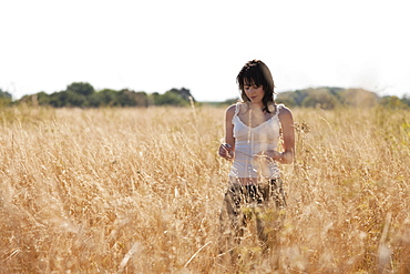 France, Picardie, Albert, Young woman strolling in cornfield, France, Picardie, Albert