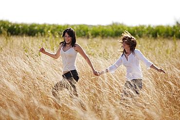 France, Picardie, Albert, Young women running through cornfield, France, Picardie, Albert