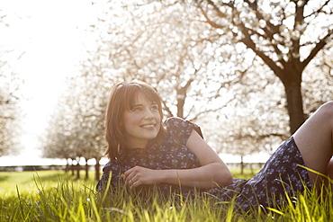Belgium, Sint-Truiden, Portrait of young woman in spring orchard, Belgium, Sint-Truiden