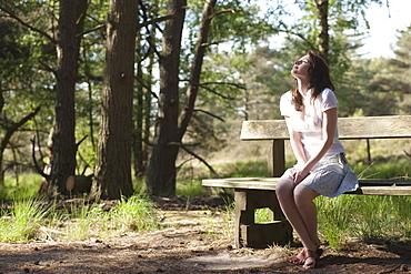 Belgium, Kalmthoutse Heide, Young woman sitting on bench, Kalmthoutse Heide (near Antwerpen), Belgium