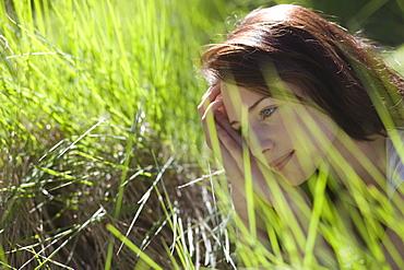 Young woman among green grass