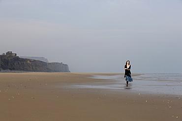 France, Pas-de-Calais, Escalles, Young woman strolling on empty beach, France, Pas-de-Calais, Escalles