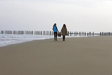 France, Pas-de-Calais, Escalles, Two women strolling on empty beach, France, Pas-de-Calais, Escalles