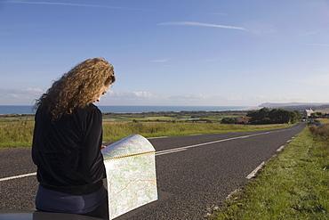 France, Pas-de-Calais, Escalles, Young woman reading map on roadside, France, Pas-de-Calais, Escalles