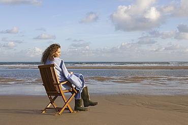 France, Pas-de-Calais, Escalles, Young woman sitting on chair on empty beach, France, Pas-de-Calais, Escalles