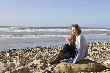 France, Pas-de-Calais, Escalles, Woman wrapped in blanket sitting on rocky beach, France, Pas-de-Calais, Escalles