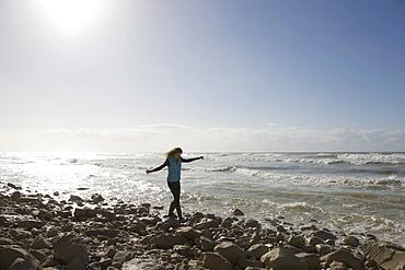 France, Pas-de-Calais, Escalles, Young woman strolling on rocky beach, France, Pas-de-Calais, Escalles
