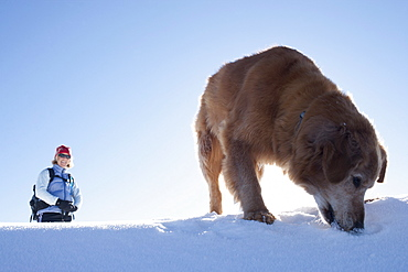 Woman hiking with her dog in winter scenery