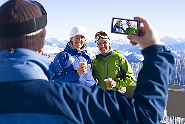 USA, Montana, Whitefish, Man photographing two women in mountain resort