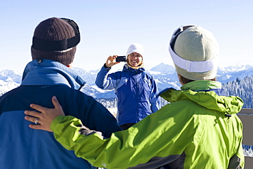 USA, Montana, Whitefish, Woman photographing friends in mountain resort
