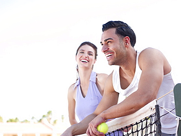 Smiling couple standing near tennis net
