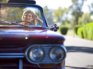 Young woman driving classic's car