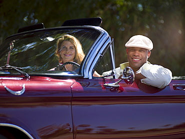 Smiling couple driving classic's car