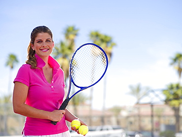Young woman with tennis balls and racket