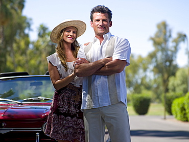 Smiling couple standing near convertible car