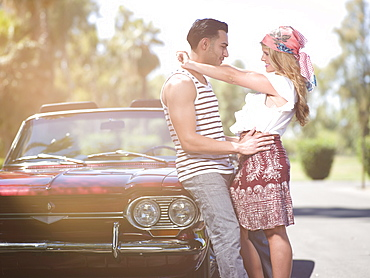 Couple embracing near convertible car