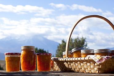 Basket full of jars with preserves