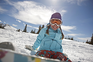 USA, Colorado, Telluride, Girl (10-11) posing with snowboard in winter scenery