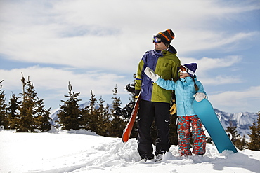 USA, Colorado, Telluride, Father and daughter (10-11) standing with snowboards in winter scenery