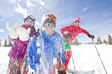 USA, Colorado, Telluride, Grandparents with girl (10-11) throwing snowballs at camera