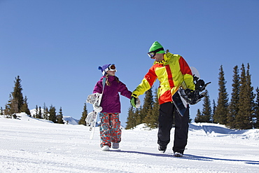 USA, Colorado, Telluride, Father and daughter (10-11) walking with snowboards in winter scenery