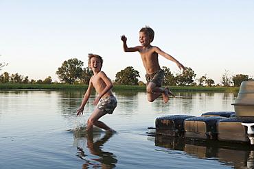 USA, Texas, Texarkana, Two boys (8-9) jumping into lake