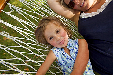 Portrait of girl (4-5) with mother in hammock