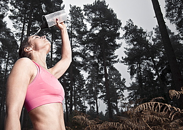 England, Suffolk, Female athlete pouring water on head, Thetford Forest