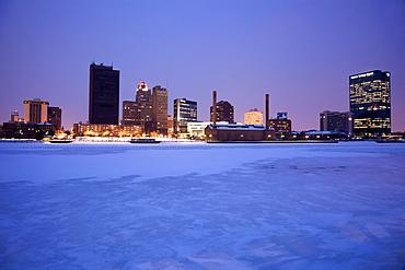 USA, Ohio, Toledo skyline across frozen river, dusk