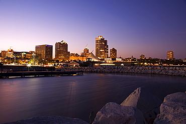 USA, Wisconsin, Milwaukee skyline across lake at dusk
