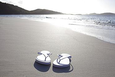 United States Virgin Islands, St. John, Pair of flip flops left on empty beach, United States Virgin Islands, St. John