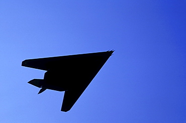 Silhouette of military plane flying against blue sky, Holland