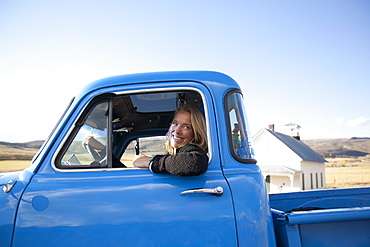 USA, Colorado, Carbondale, Cowgirl driving old fashioned pickup truck