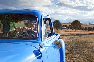 USA, Colorado, Carbondale, Cowgirl driving old fashioned pickup truck in field