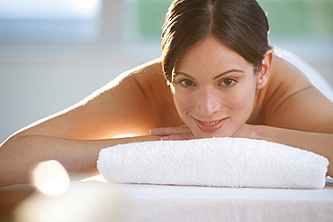 Mid-adult woman lying on massage table with candle in foreground