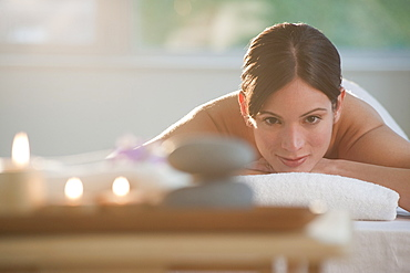Mid-adult woman lying on massage table with candles and rocks in foreground
