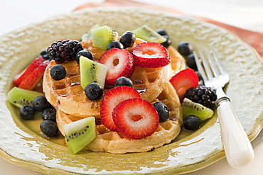 Waffles with berries and kiwi on plate