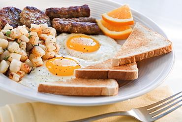 Fried sausages on plate with eggs and plates in background