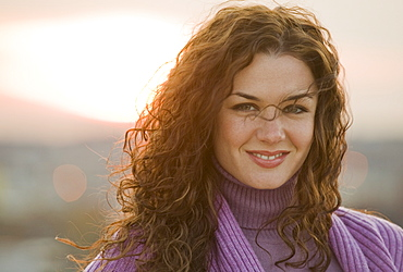 Portrait of smiling woman with sunset in background