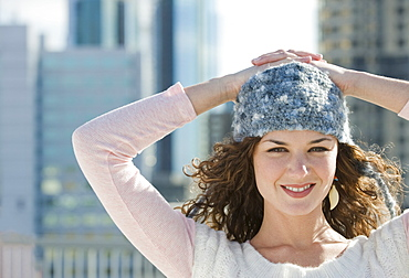 Portrait of woman in stocking cap with city in background