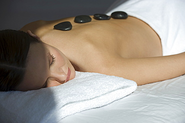 Woman laying on massage table with warm stones on back