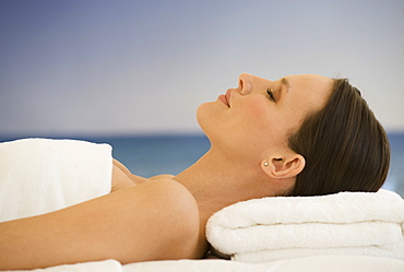 Woman laying on massage table with ocean in background