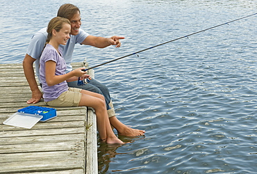 Father and daughter fishing off dock