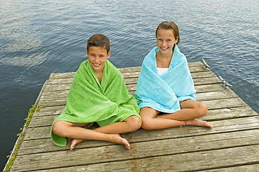 Children wrapped in towels on dock