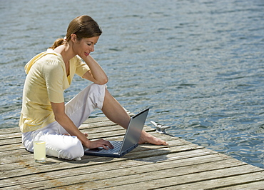 Woman using laptop on dock