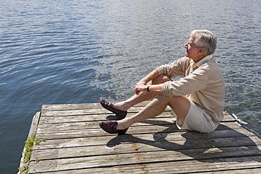Senior man sitting on dock