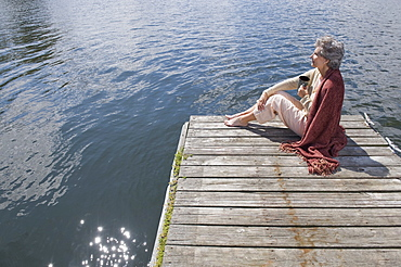 Senior woman sitting on dock