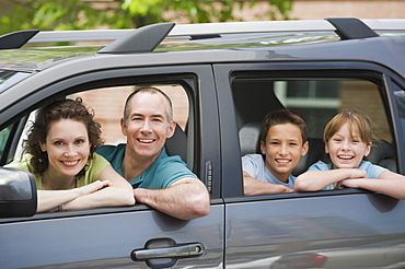 Family with two children looking out car windows
