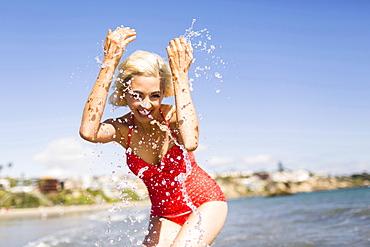 Woman in red swimming costume splashing water on beach, Costa Mesa, CA