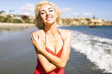 Portrait of woman wearing red swimming costume on beach, Costa Mesa, CA